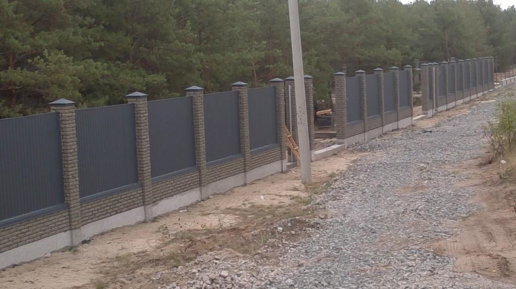 Комбинированный забор из профнастила с кирпичными столбами.